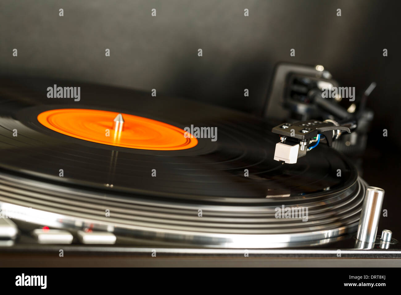 Turntable rotates together with vinyl record on - Stock Image