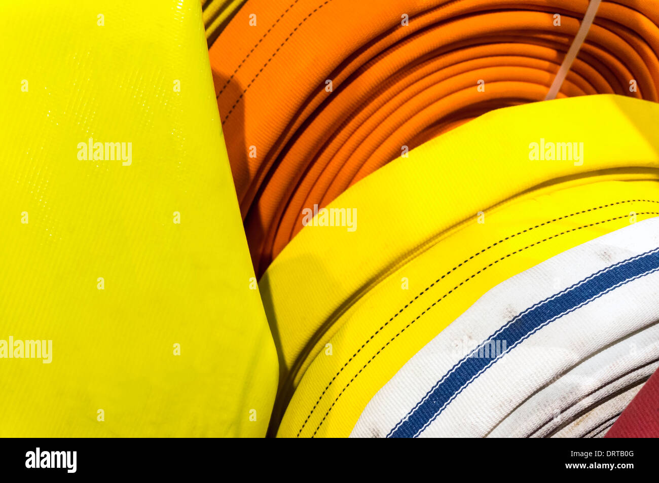Coiled fire hoses display at trade show. - Stock Image
