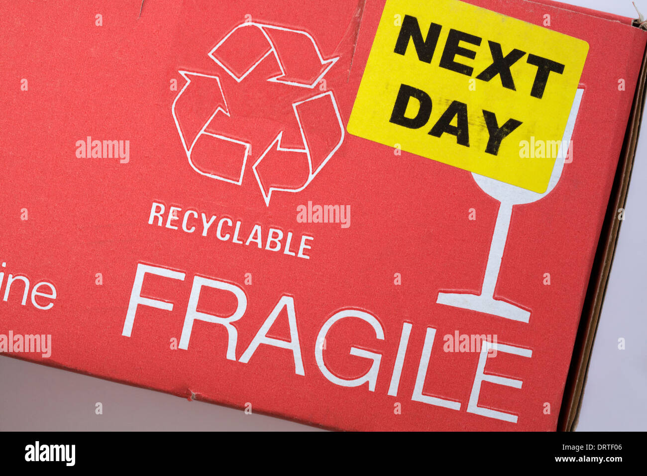 next day sticker, recyclable logo and fragile glass information on cardboard box - Stock Image