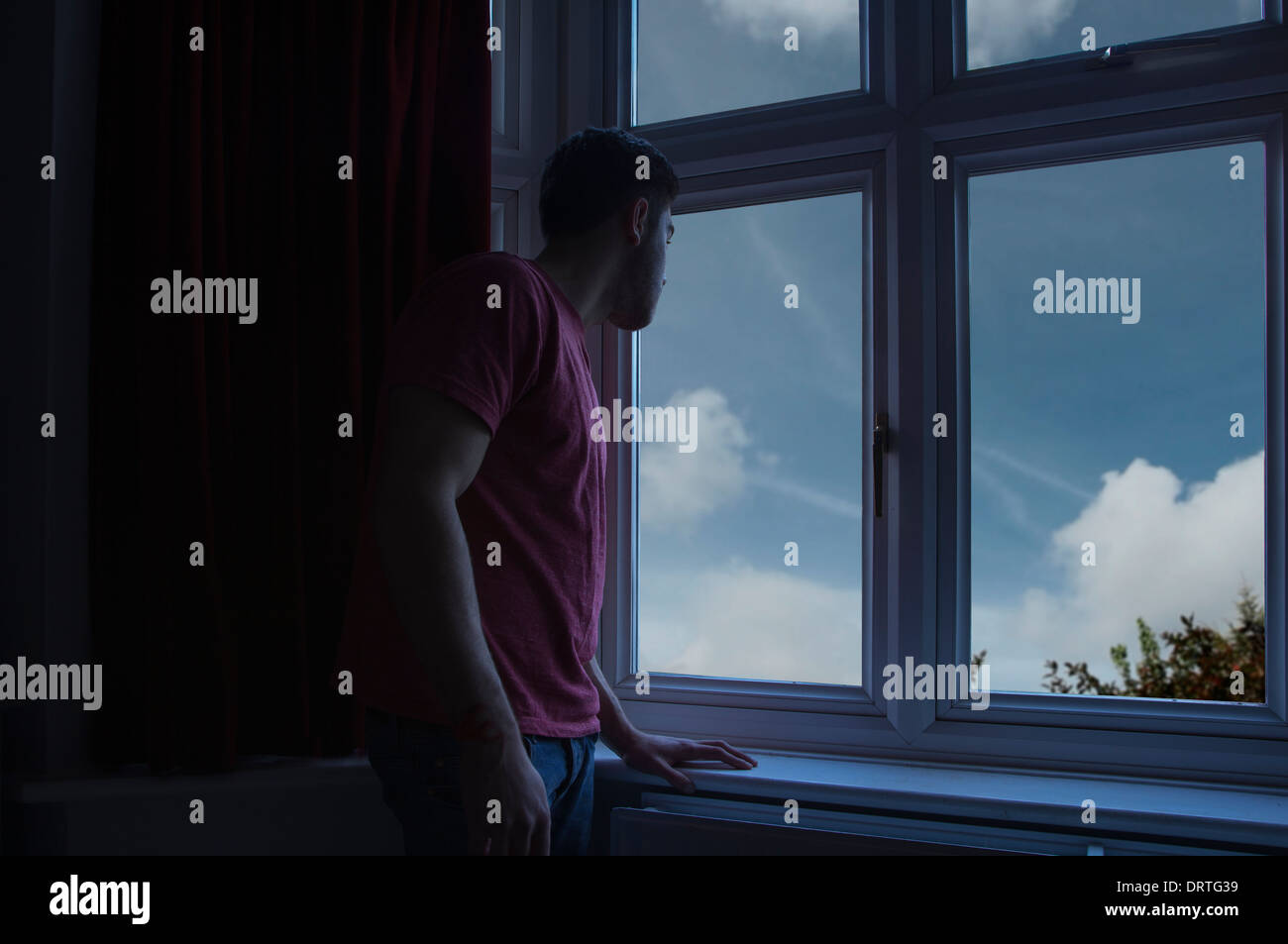 Young man in a dark room looking out through a window. - Stock Image