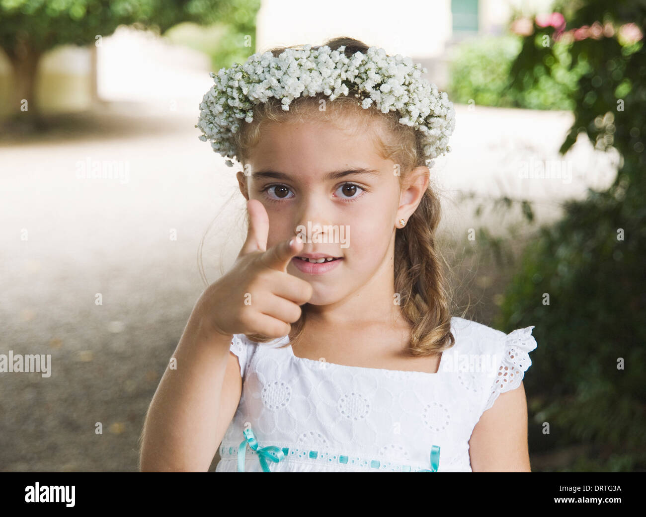 Little girl dressed for a wedding. The girl is making a hand gesture. - Stock Image