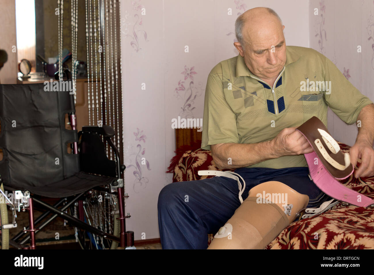 Senior man sitting on his bed fitting a prosthetic leg following an above the knee amputation sorting out the attachment straps - Stock Image