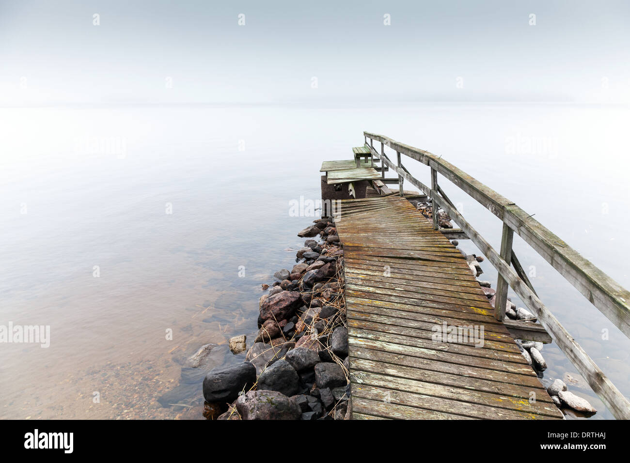 Old ruined wooden pier. Saimaa lake in foggy morning Stock Photo