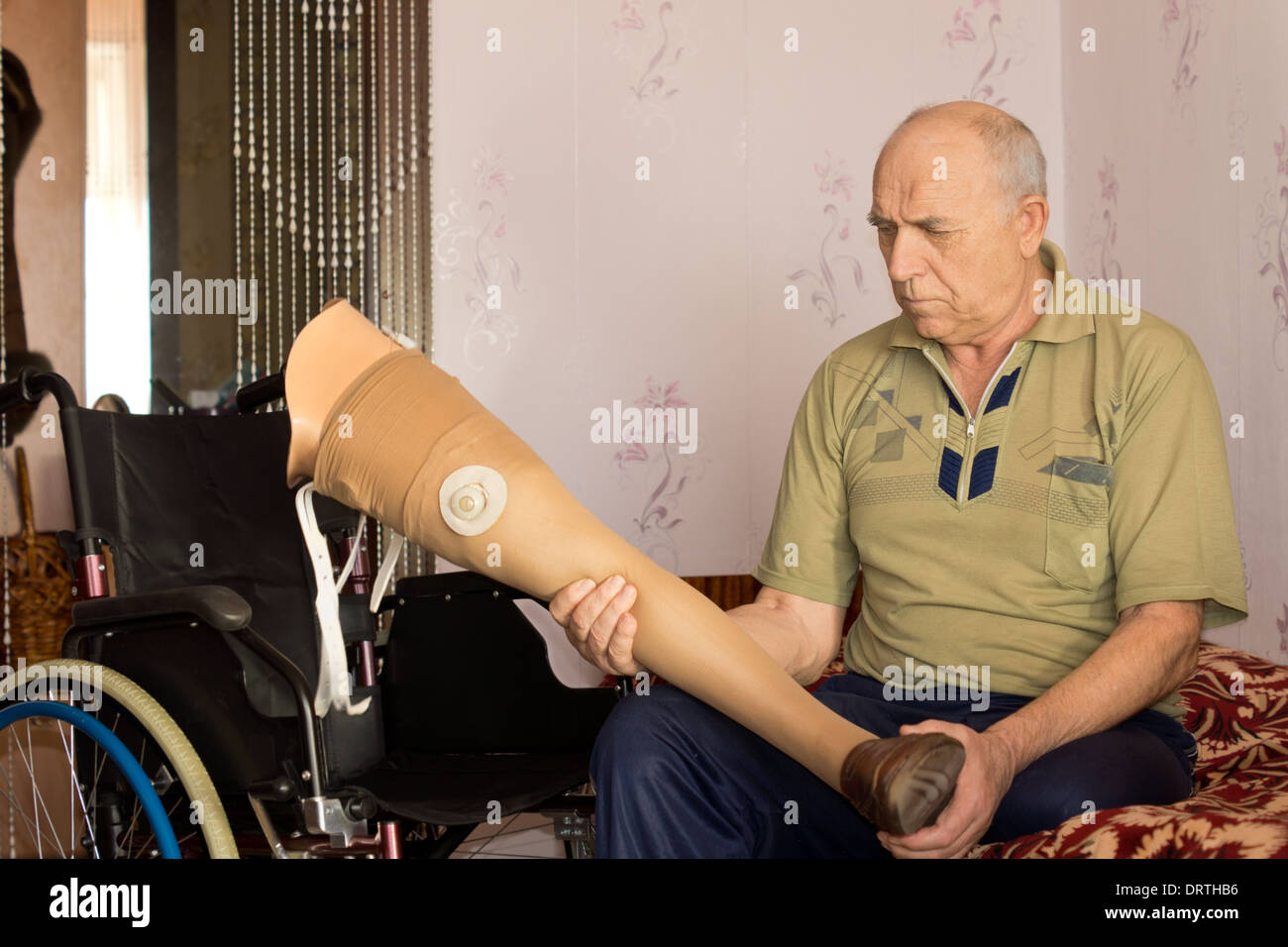 Senior disabled man sitting on a bed alongside his wheelchair holding a prosthetic leg or artificial limb - Stock Image