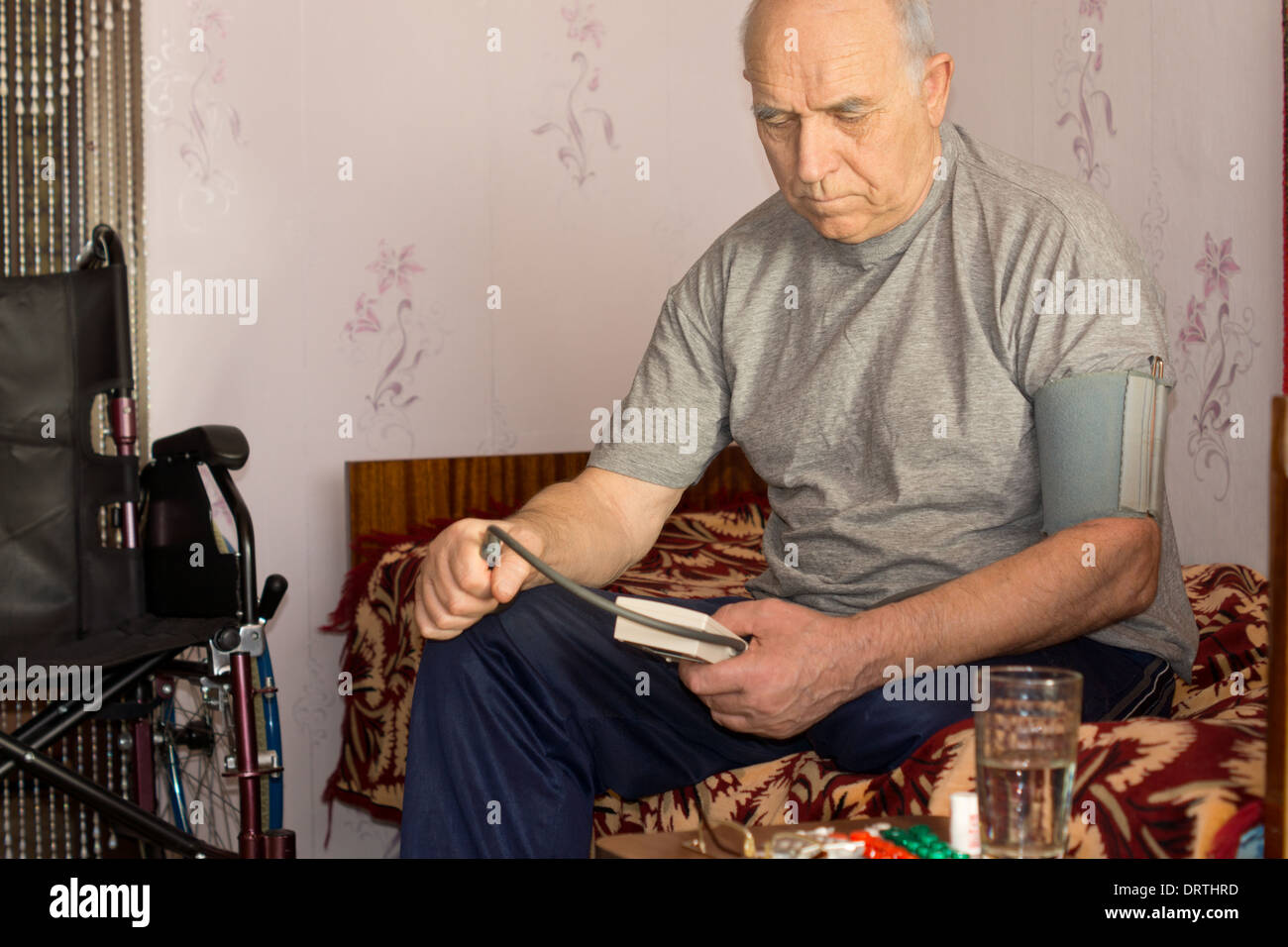 Senior disabled man taking his own blood pressure sitting on his bed alongside his wheelchair using a pressure cuff and sphygmomanometer. - Stock Image