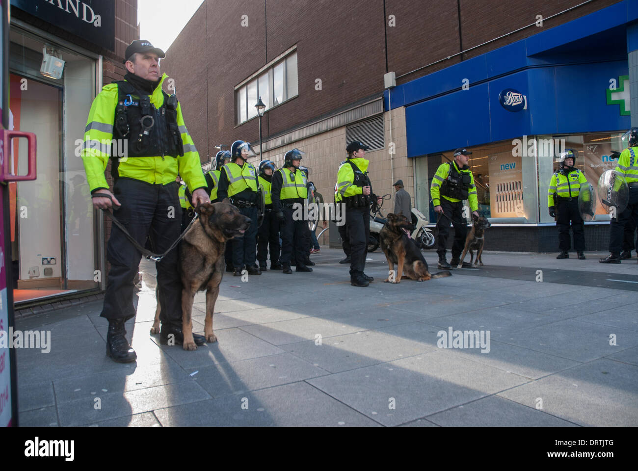 Slough, UK . 01st Feb, 2014. Police in riot gear and dog handlers' cordon off a side street during an English Defence League march in Slough, United Kingdom. Credit:  Peter Manning/Alamy Live News - Stock Image