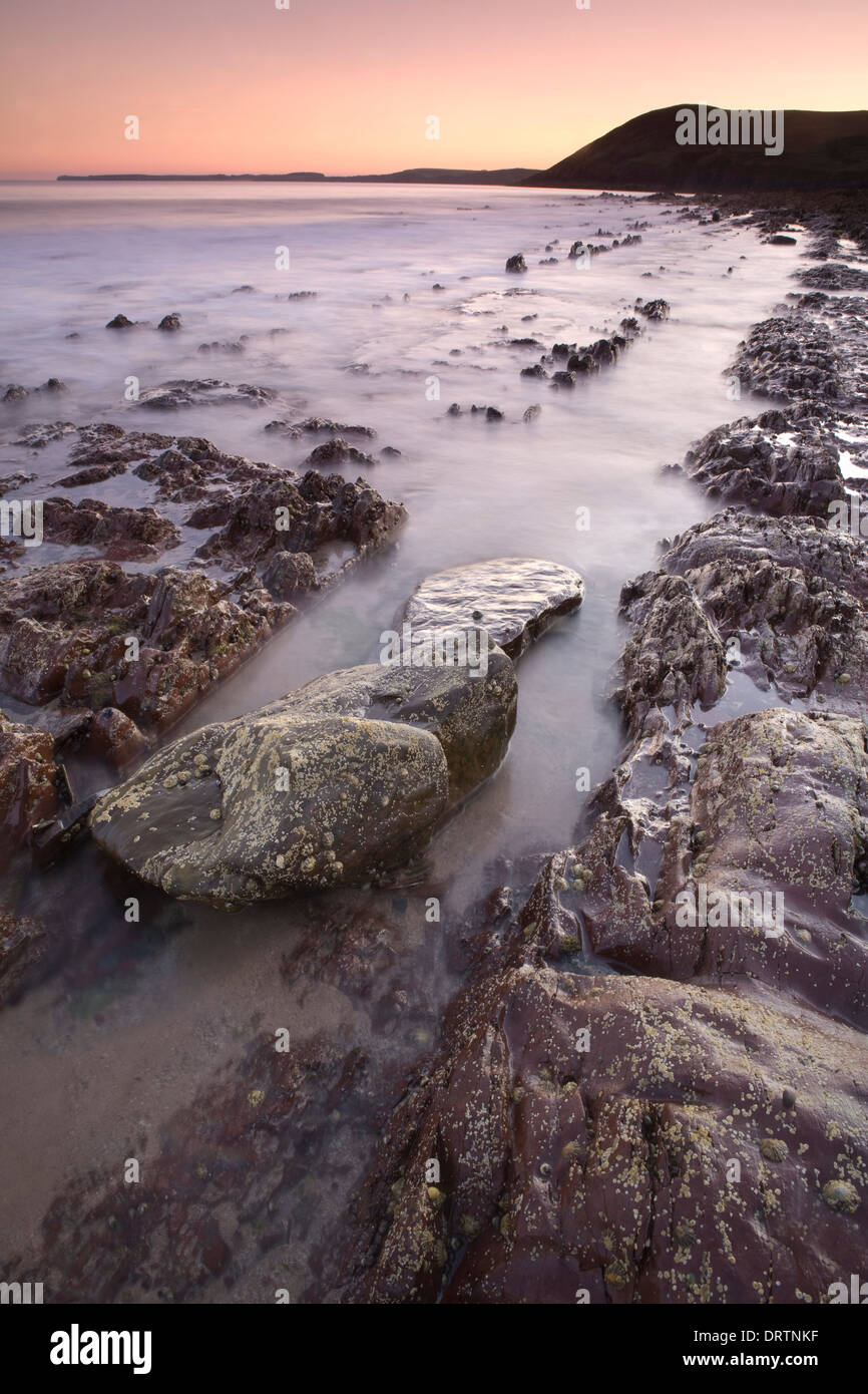 Jagged rocks being covered by the incoming tide at sunset on Manorbier beach, Pembrokeshire, South Wales, UK Stock Photo
