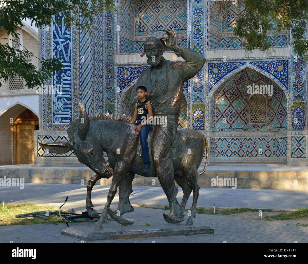Young boy posing for a photo with Hodja Nasreddin statue, Lyabi Hauz Square Bukhara, UZbekistan - Stock Image