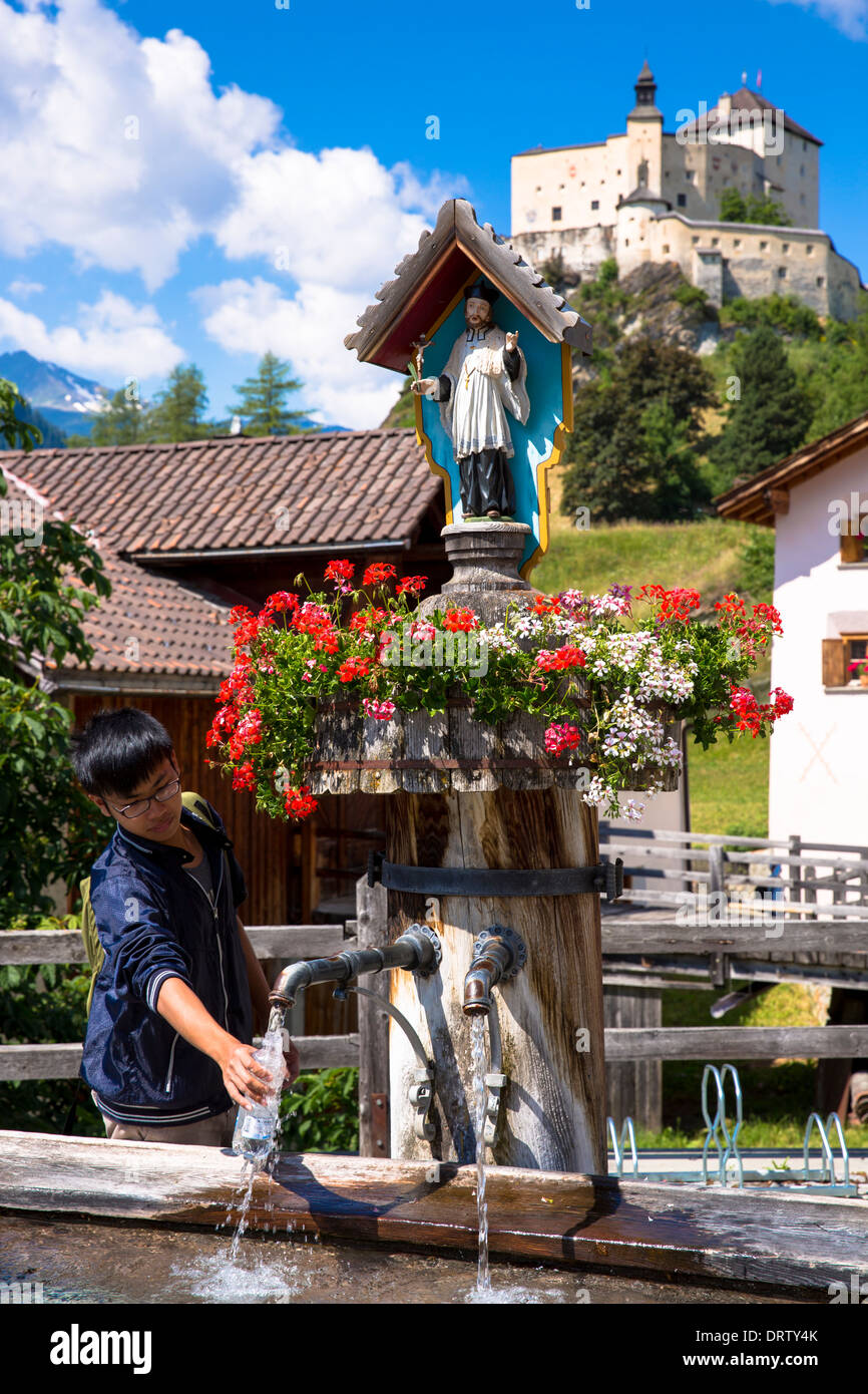 Tourist filling bottle from water fountain on a visit toTarasp Castle in the Lower Engadine Valley, Switzerland - Stock Image