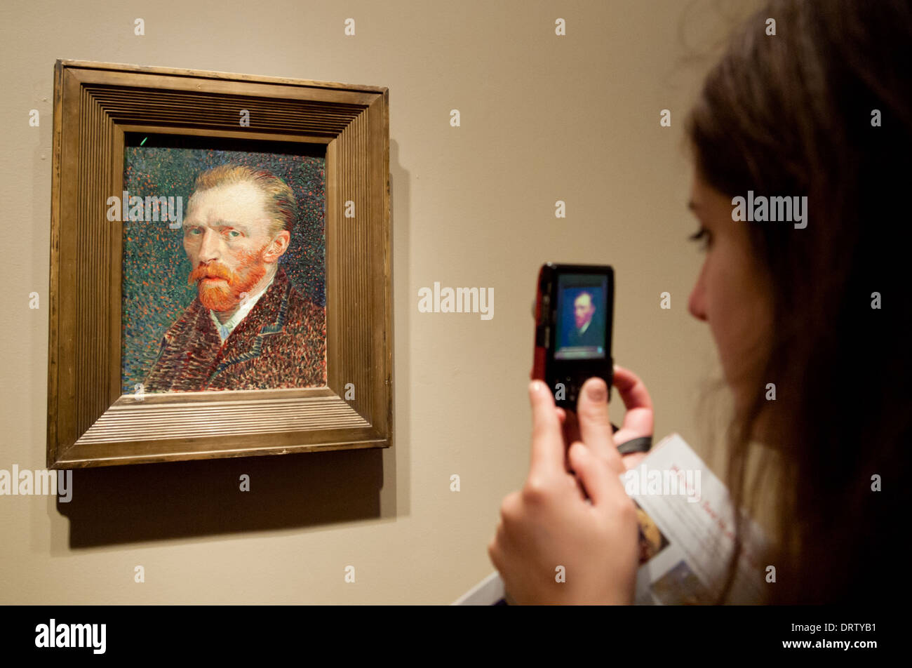A pretty brunette girl takes a picture of 'Self-Portrait', by Vincent van Gogh, in The Art Institute of Chicago art museum. - Stock Image