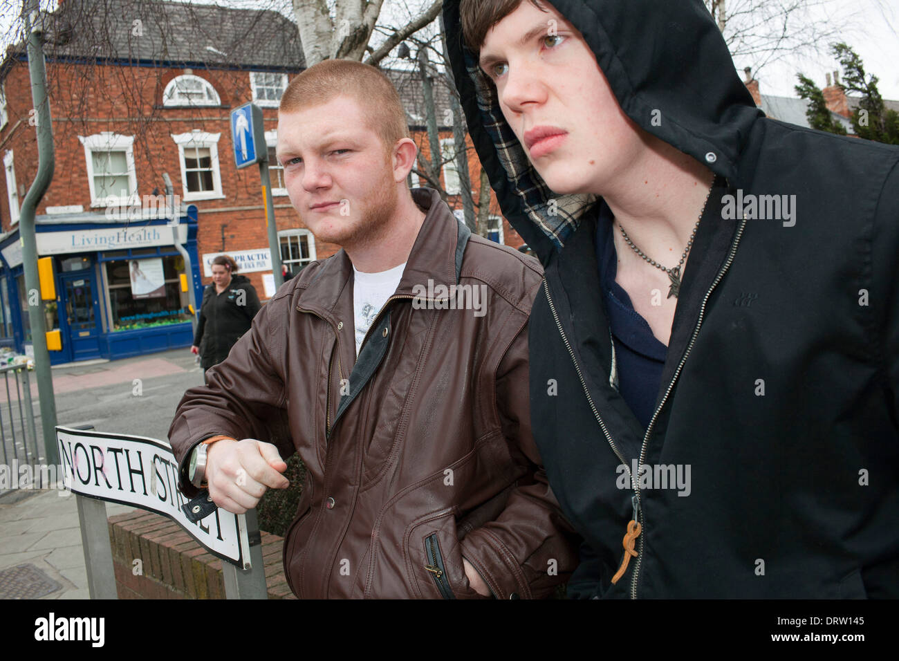 Two men in their early 20's on a street corner in the town of Grantham. - Stock Image