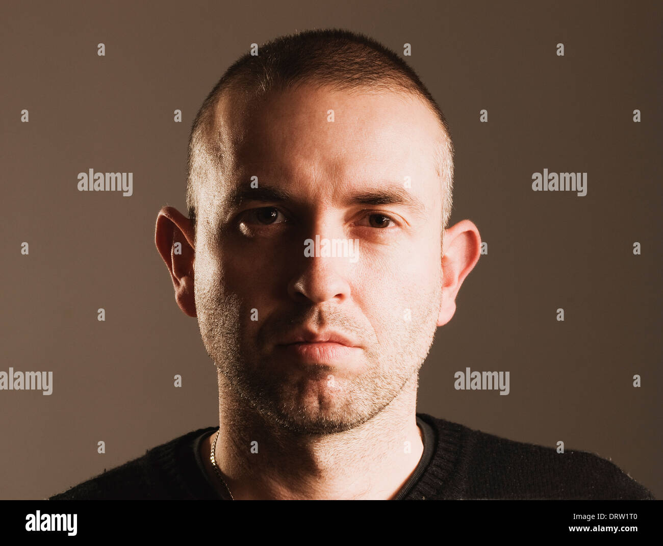 Man with seriously expression, looking and camera and isolated over dark background Stock Photo