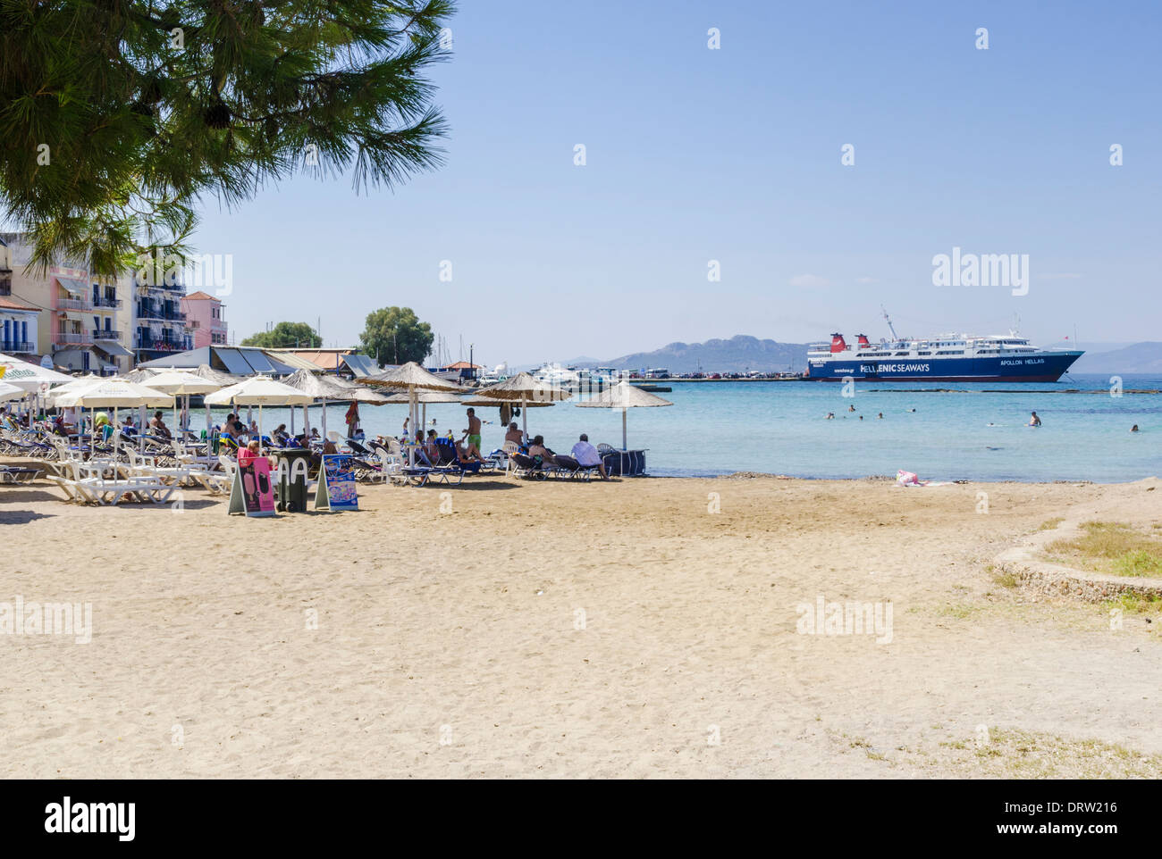 People on Avra beach with a ferry in the background, Aegina Town, Aegina Island, Greece - Stock Image