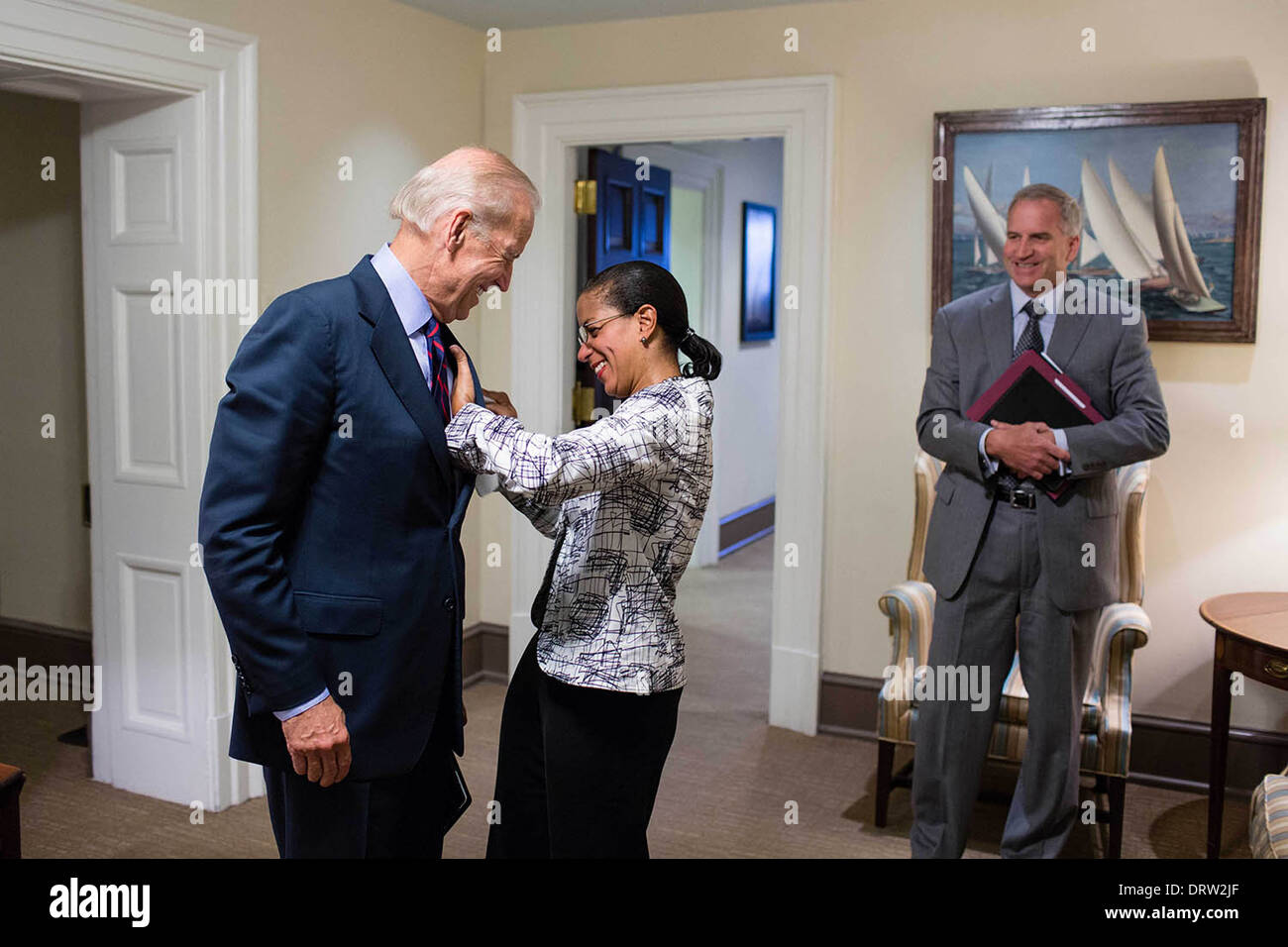 National Security Advisor Susan Rice helps Vice President Joe Biden with a spot on his suit jacket, in a hall outside the Oval Office August 2, 2013 in Washington, DC. Robert Cardillo, Deputy Director of National Intelligence for Intelligence Integration, watches at right. - Stock Image