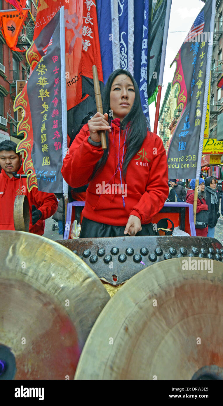 Lady drummer marching in the Chinese New Year parade on Mott Street in Chinatown, New York City. - Stock Image