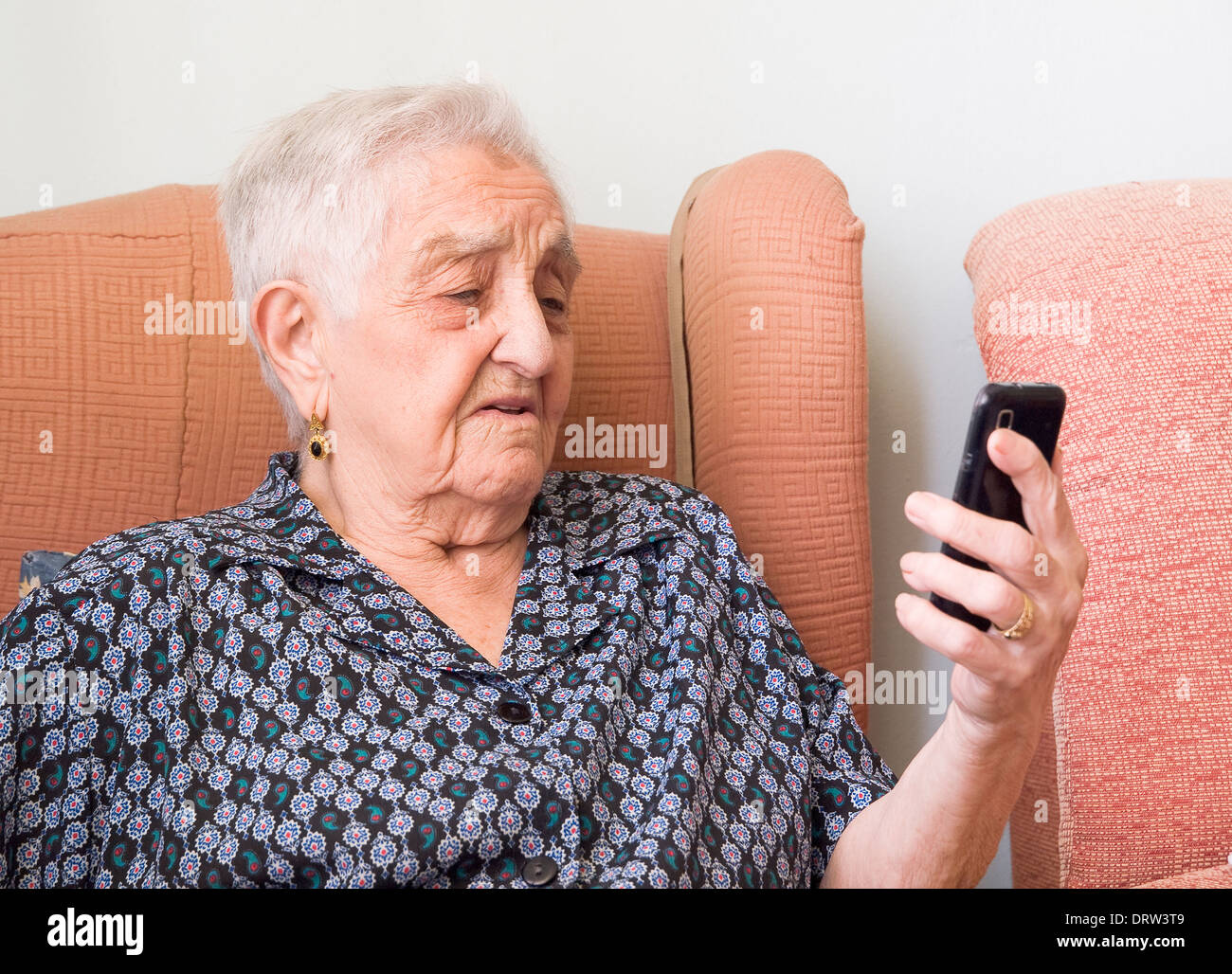 Elderly woman looking at a smartphone with confused expression. The woman is in her home. - Stock Image