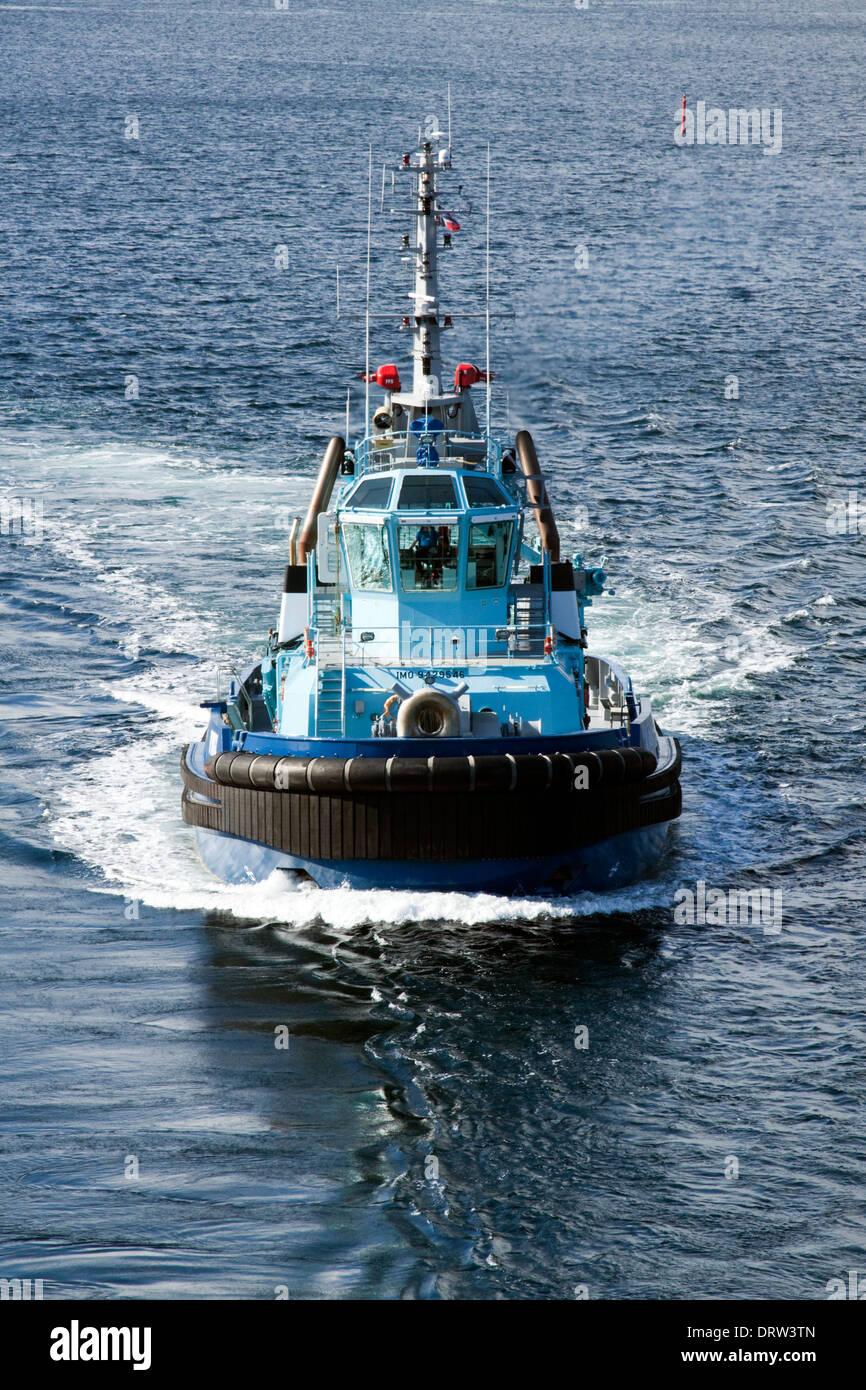 Tug 'Vivax' at sea near Alesund - preparing to manoeuvre cruise ship - Stock Image