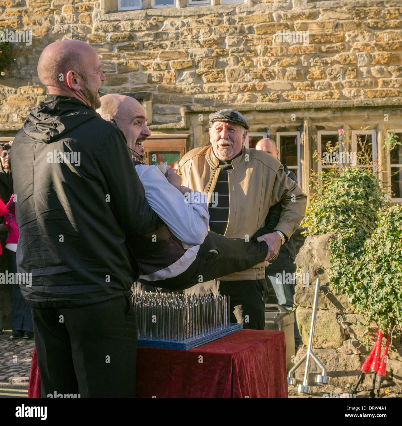 Street Entertainer being placed on a bed of nails by members of the audience  at the Grassington Dickensian Festival, 2013. - Stock Image