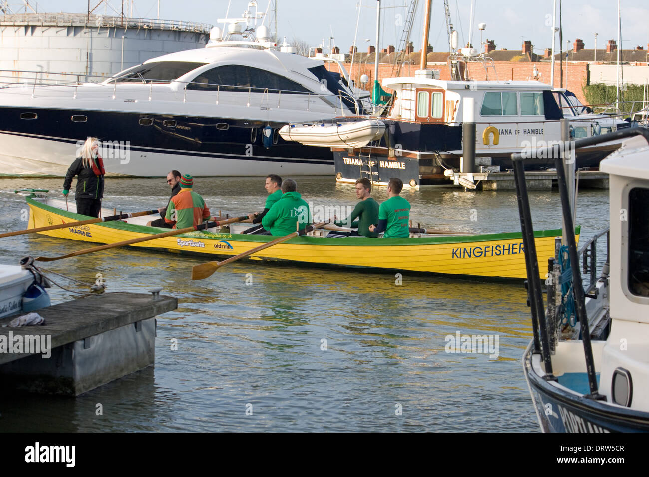 Gig boat with crew in Weymouth's inner harbour. - Stock Image