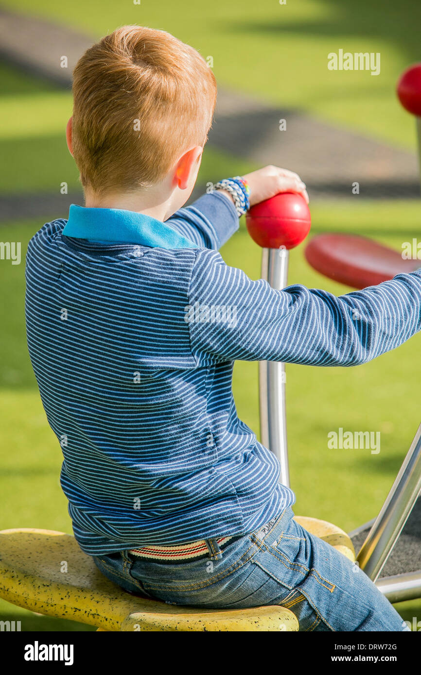 Young red haired boy plays alone in a park - Stock Image