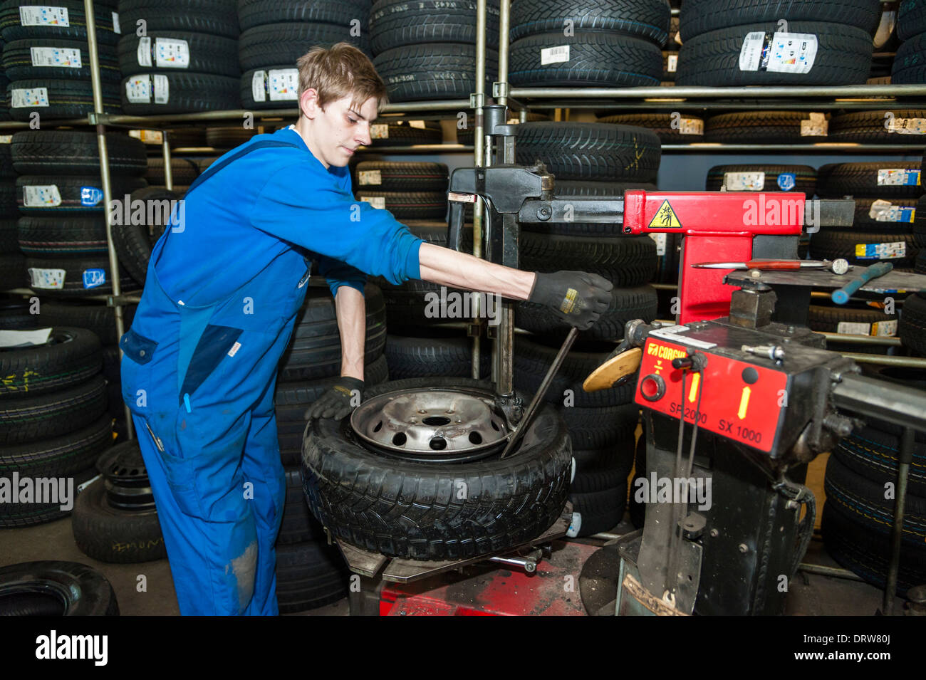 A car mechanic fits a new tyre on a wheel rim. - Stock Image