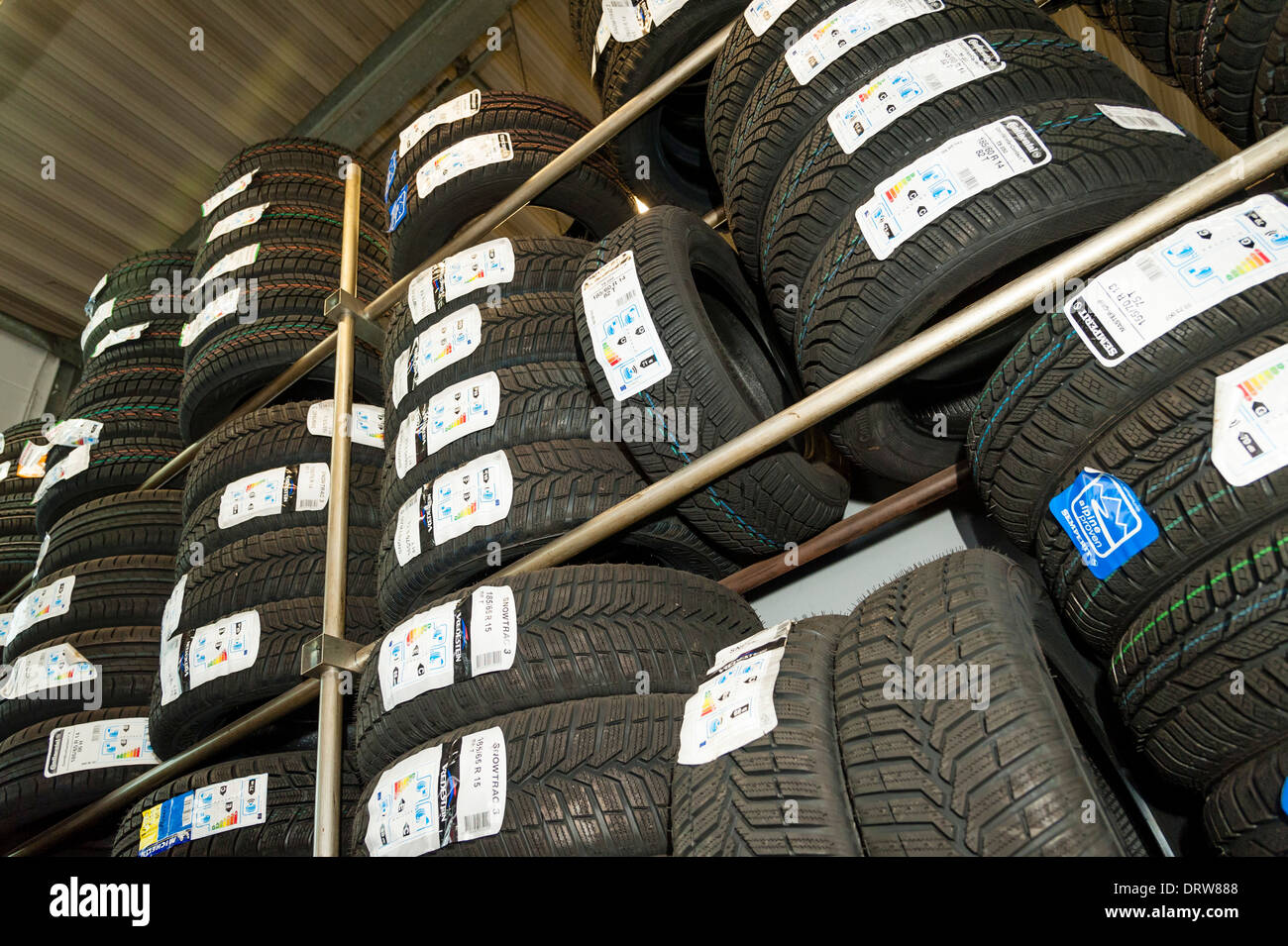 Car tires are being stored in a garage. - Stock Image