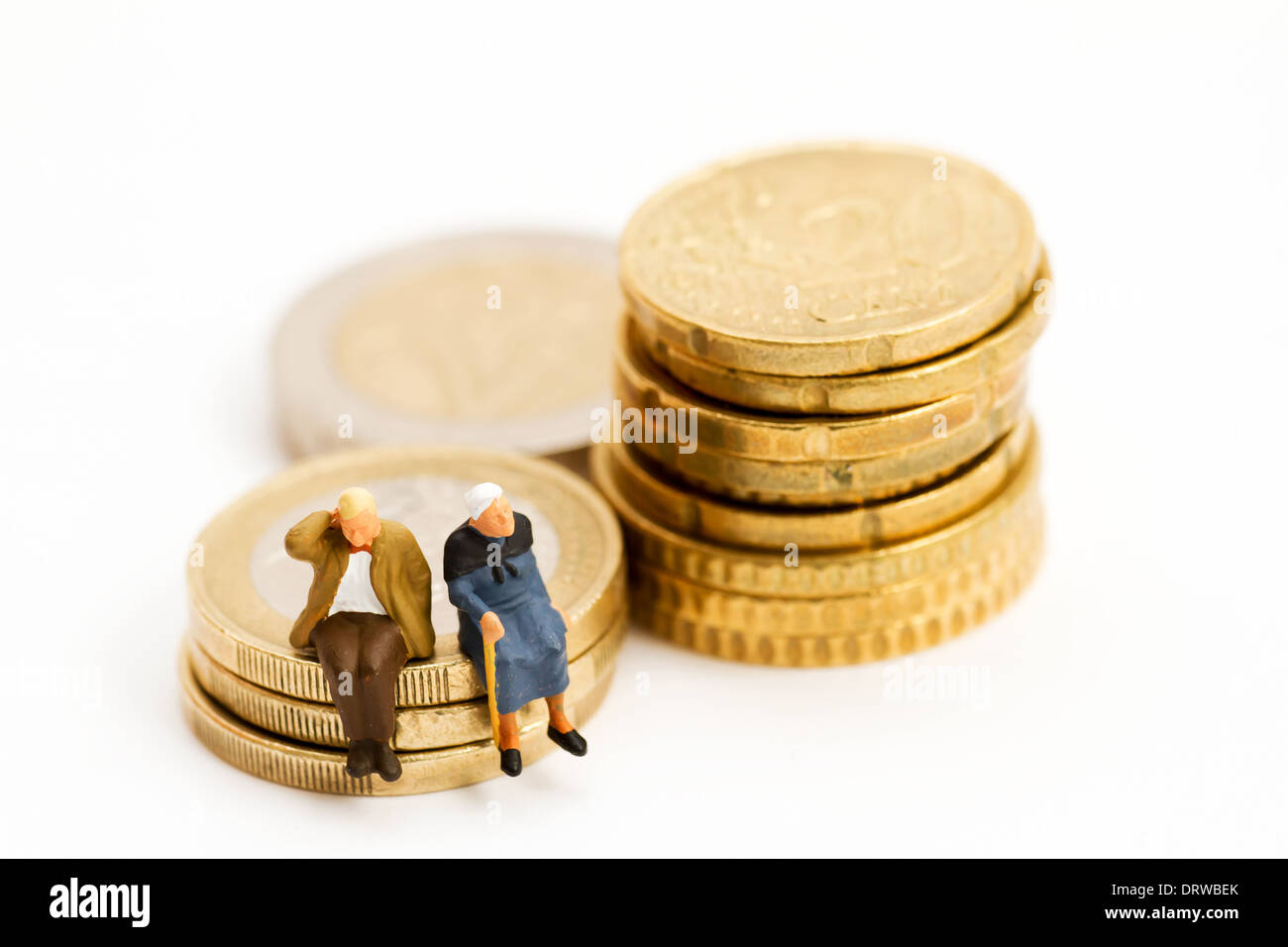 Seniors sitting on stack of coins - Stock Image