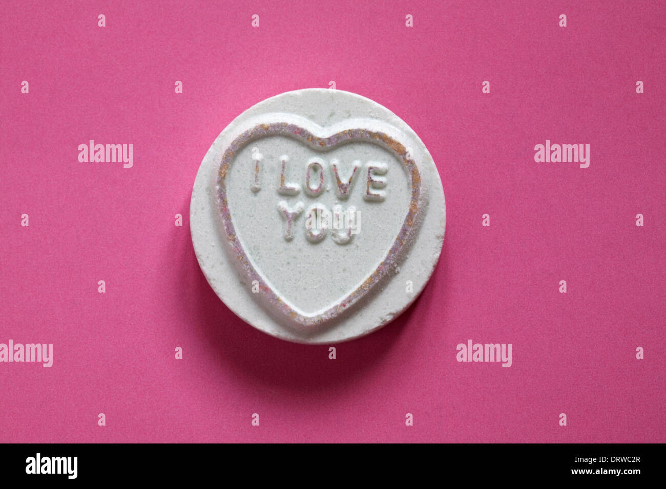 Swizzels Matlow Giant Love Hearts - individual sweet with I Love you isolated on pink background - Valentine Day message - Stock Image