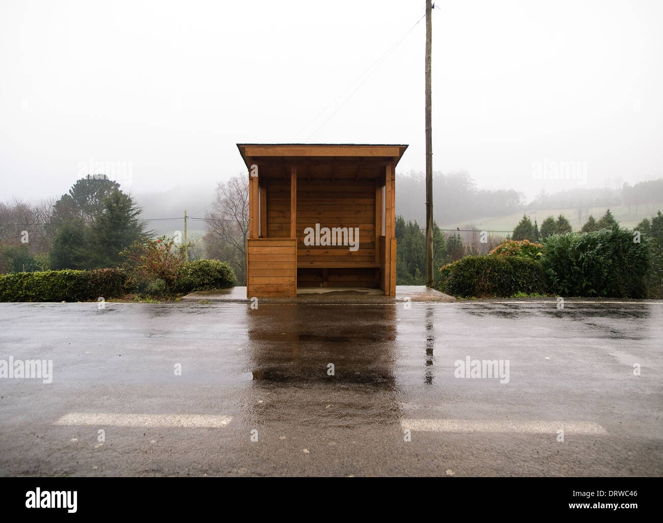 Wooden bus stop in Galicia, Spain in a misty morning. - Stock Image