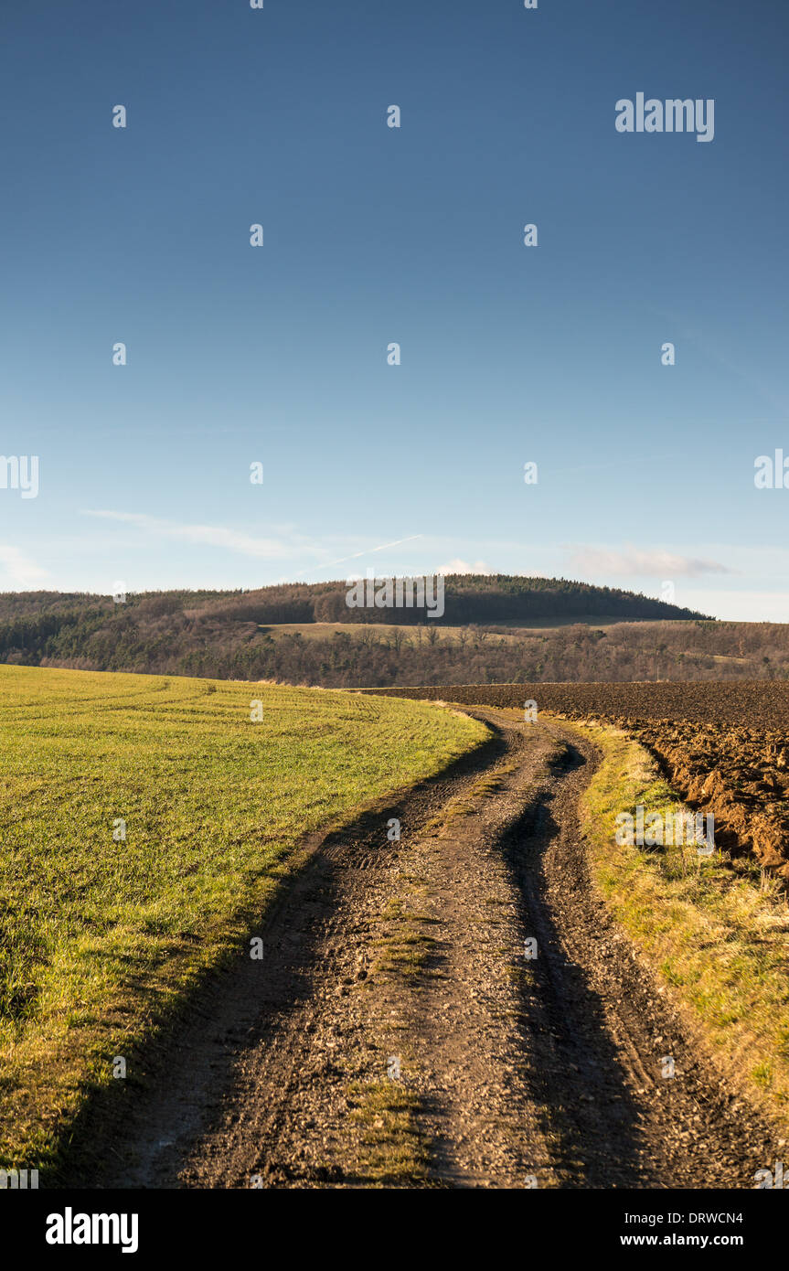 A worn dirt trail through fields in the countryside - Stock Image