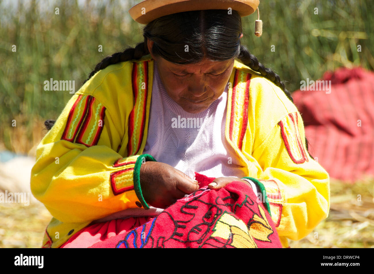 Inca woman in traditional dress embroidering colourful clothing on floating reed islands of Lake Titikaka in Peru, South America - Stock Image