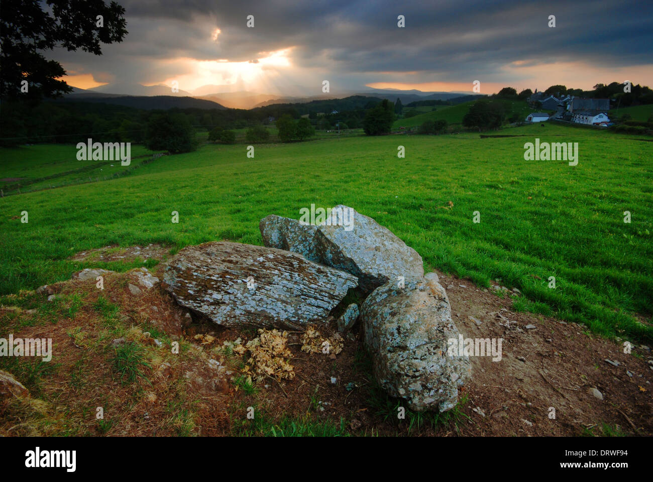 Rocks in North Wales, with sunset sky over the Snowdonia mountain range in the distance Stock Photo