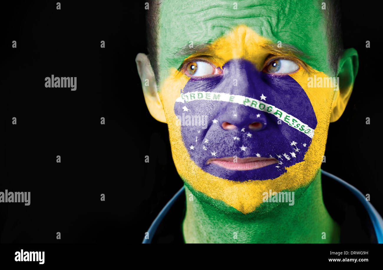A puzzled look from a football fan with their face painted with the Brazilian flag. - Stock Image