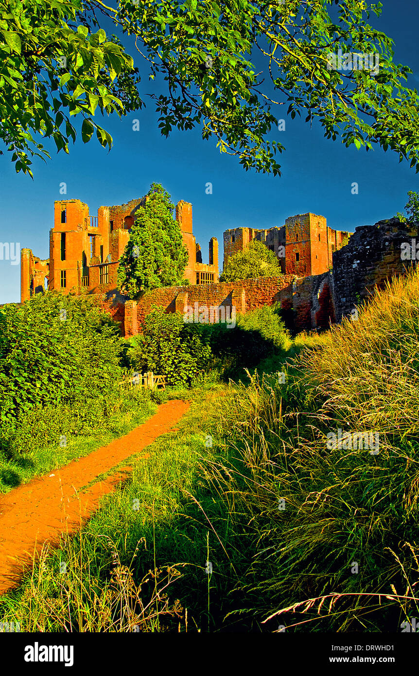 The ruined castle at Kenilworth dominates the landscape, with the red sandstone ruins forming graphic ruins. - Stock Image