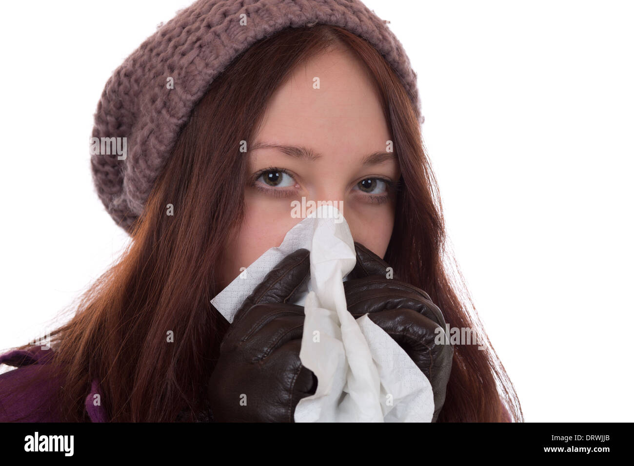 Young woman with a cold and flu virus sneezing, isolated on a white background - Stock Image