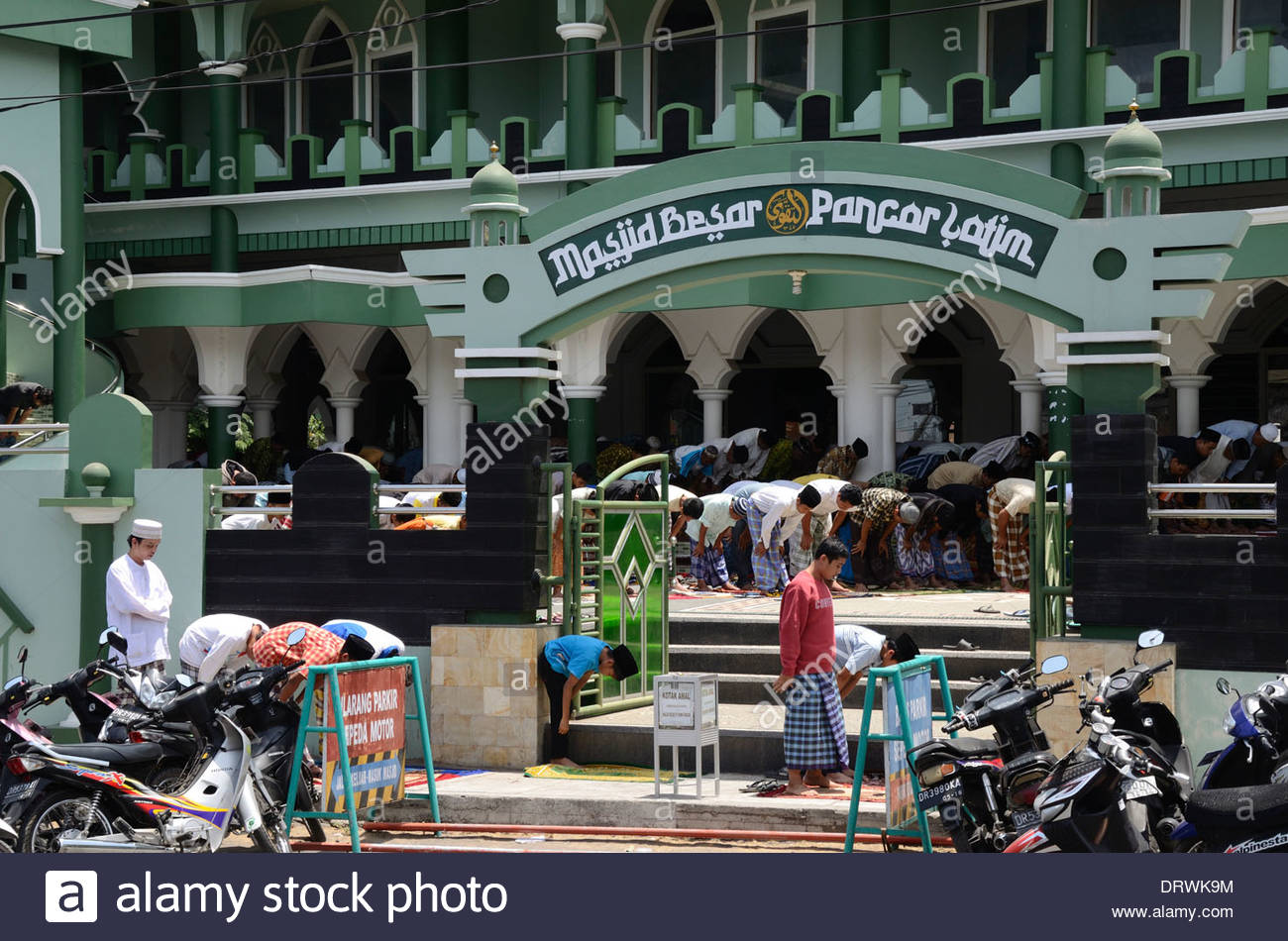 Men and boys standing in mosque and courtyard during Firday prayers Selong Lombok Timur NTB Indonesia - Stock Image