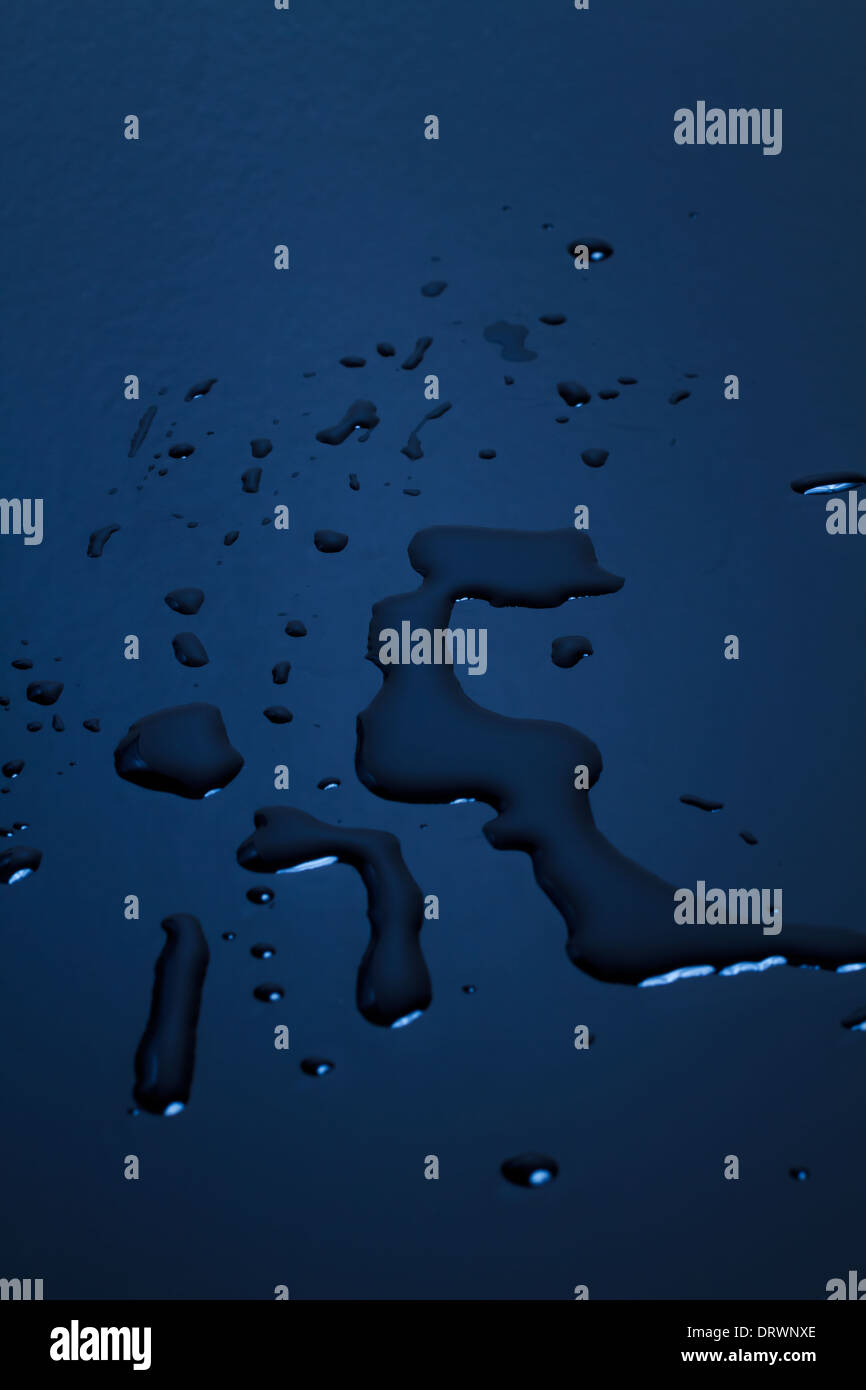 Blue surface with water droplets. - Stock Image