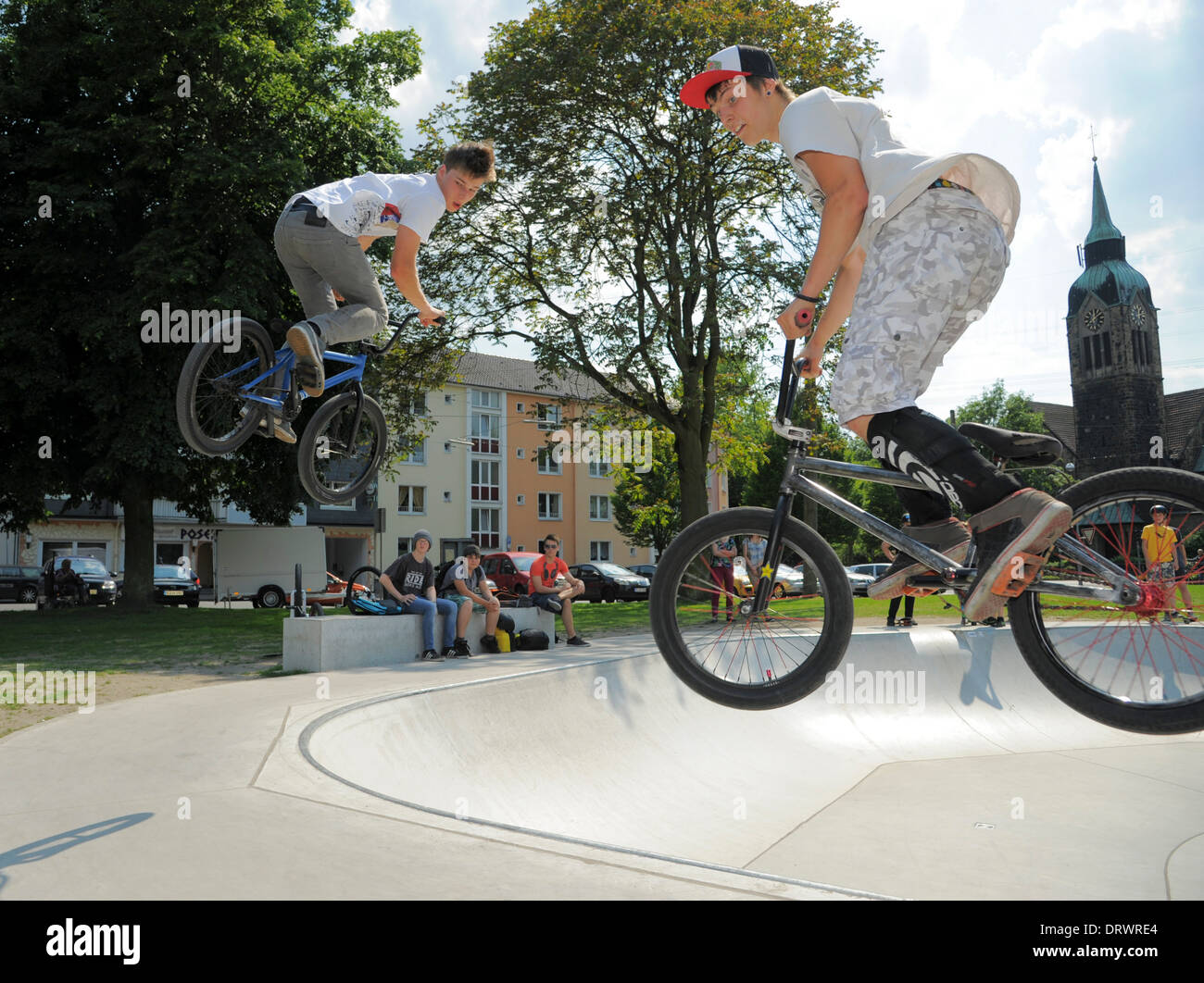 Two young bikers jump with their bikes at an urban biking park. - Stock Image
