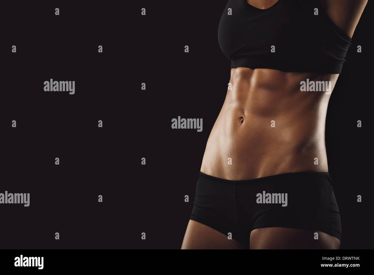 Slim and fit woman belly. Torso of fitness female. Mid section of woman body with muscular abs on black background - Stock Image