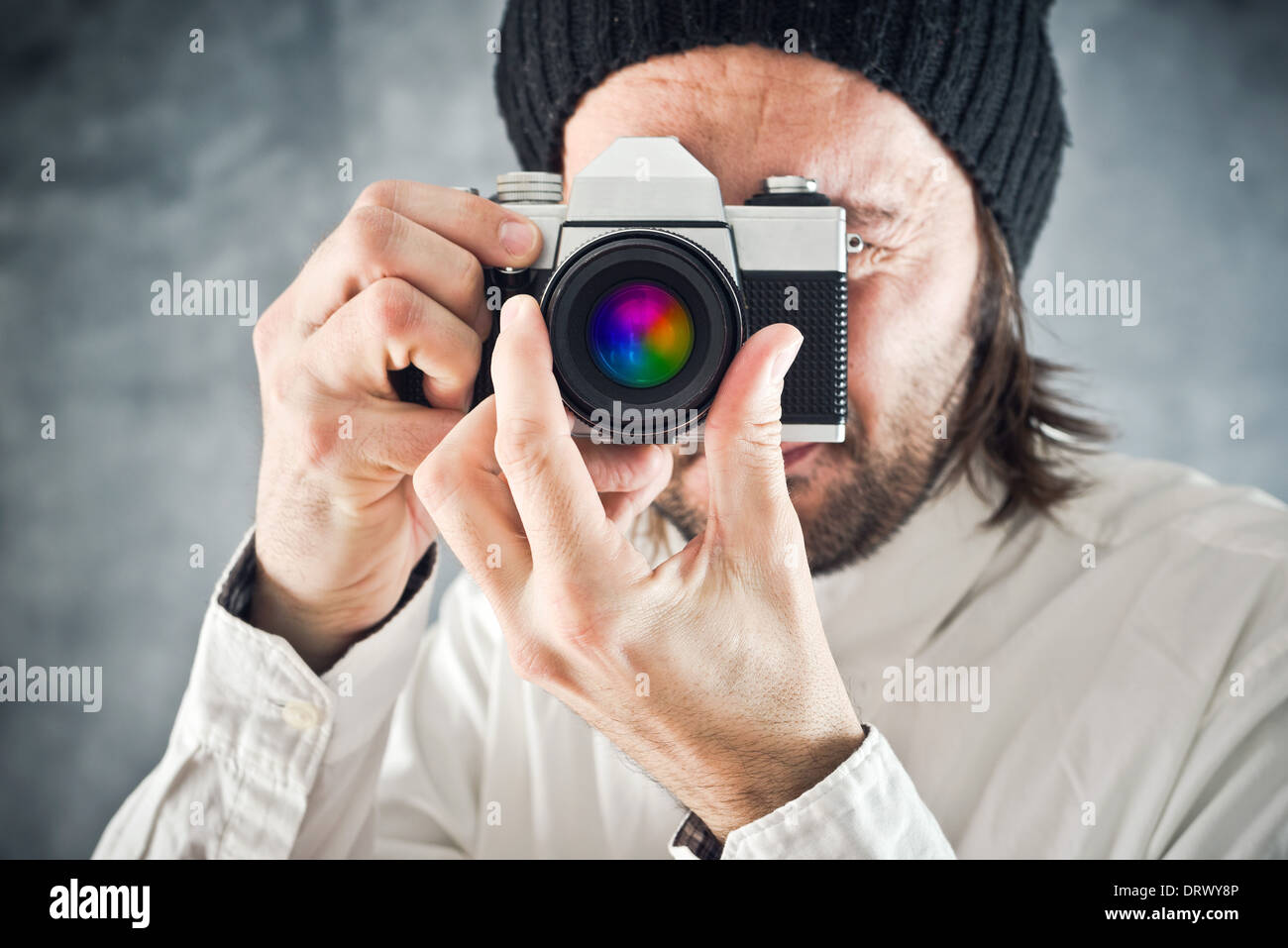 Businessman taking picture with old vintage film photo camera - Stock Image