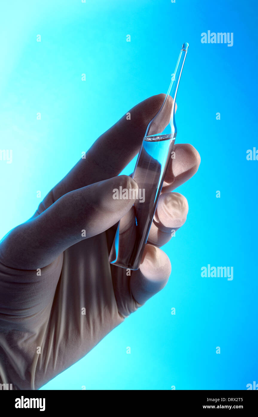 Hand in rubber glove with ampoule - Stock Image