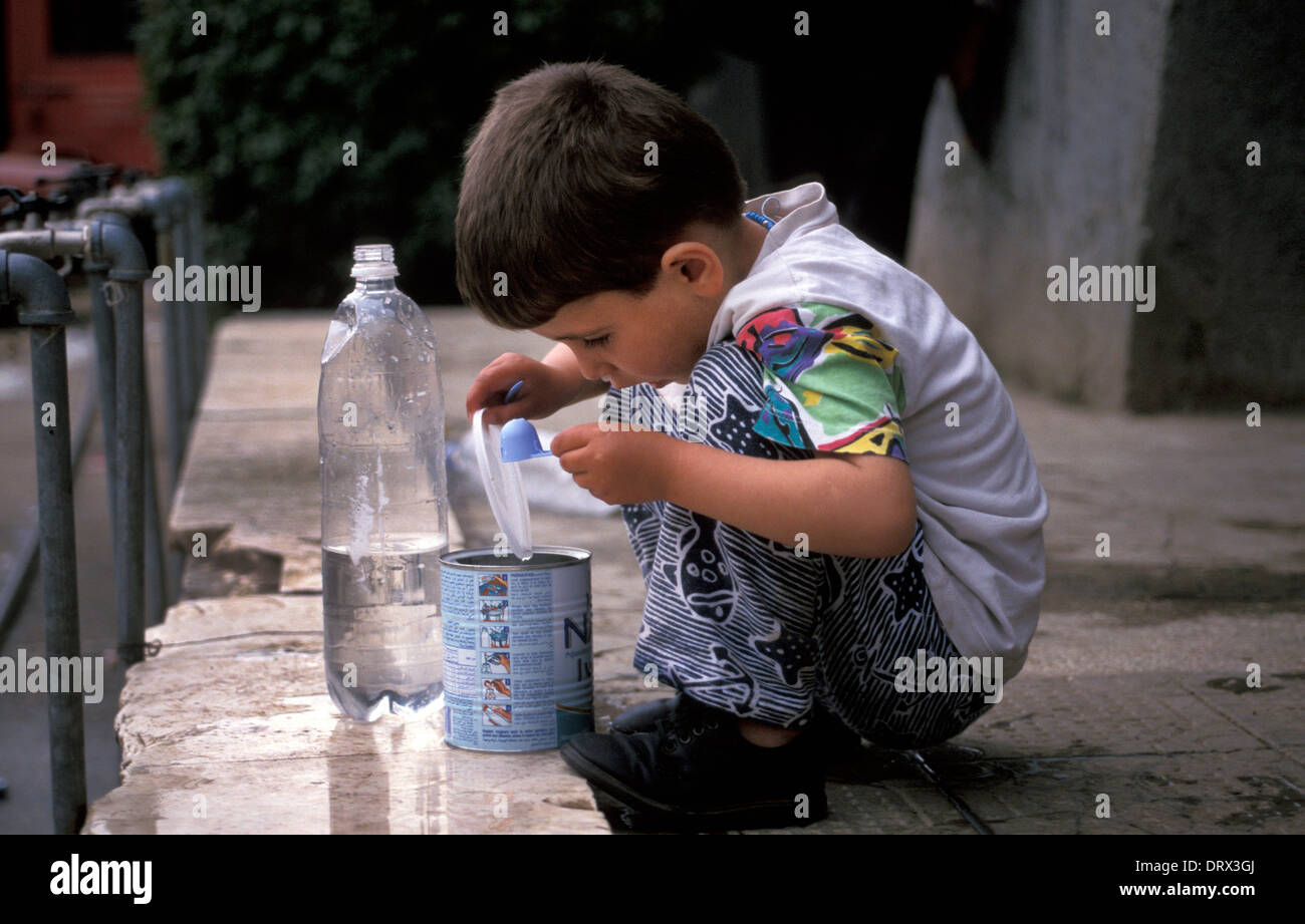 Child collecting water at refugee camp in Tirana, Albania for Kosovar refugees fleeing war in Kosovo, 1999 Stock Photo