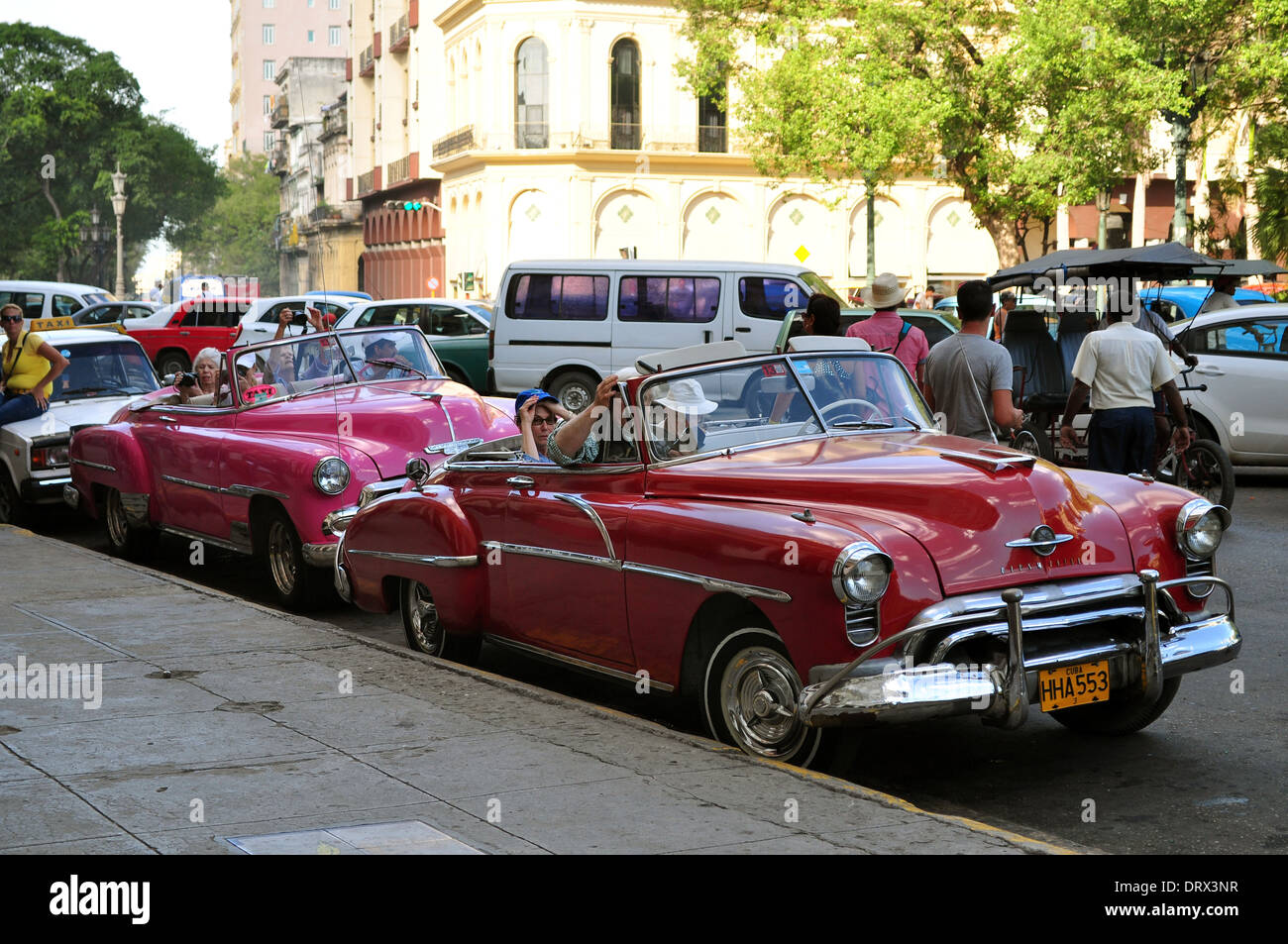 Havana, Cuba: classic restored American cars wait to take tourists around the city's sights. - Stock Image