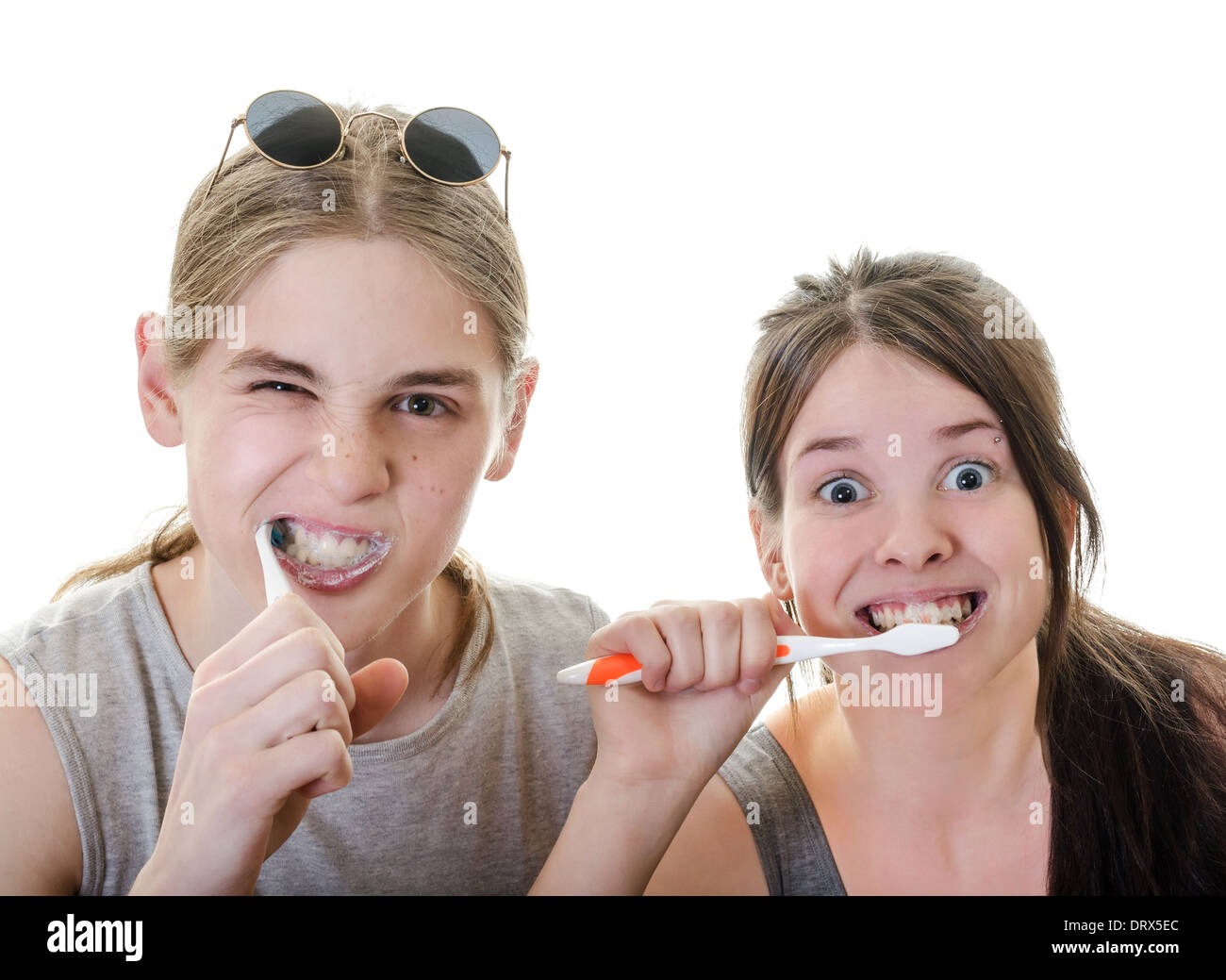 Young Couple Grimacing while Brushing their Teeth in front of camera, Horizontal Shot over White - Stock Image