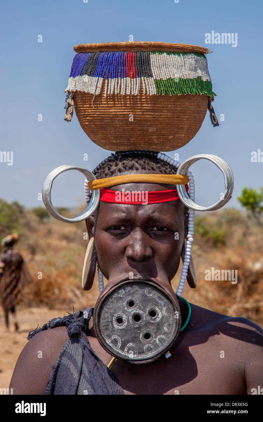 Mursi Woman Wearing A Lip Plate and Carrying A Basket On Her Head, Mursi Tribal Village, The Omo Valley, Ethiopia - Stock Image