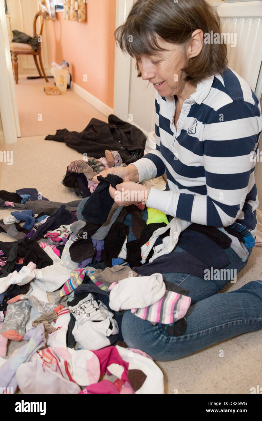 Middle aged woman sorting socks in her house, example of household jobs, UK - Stock Image