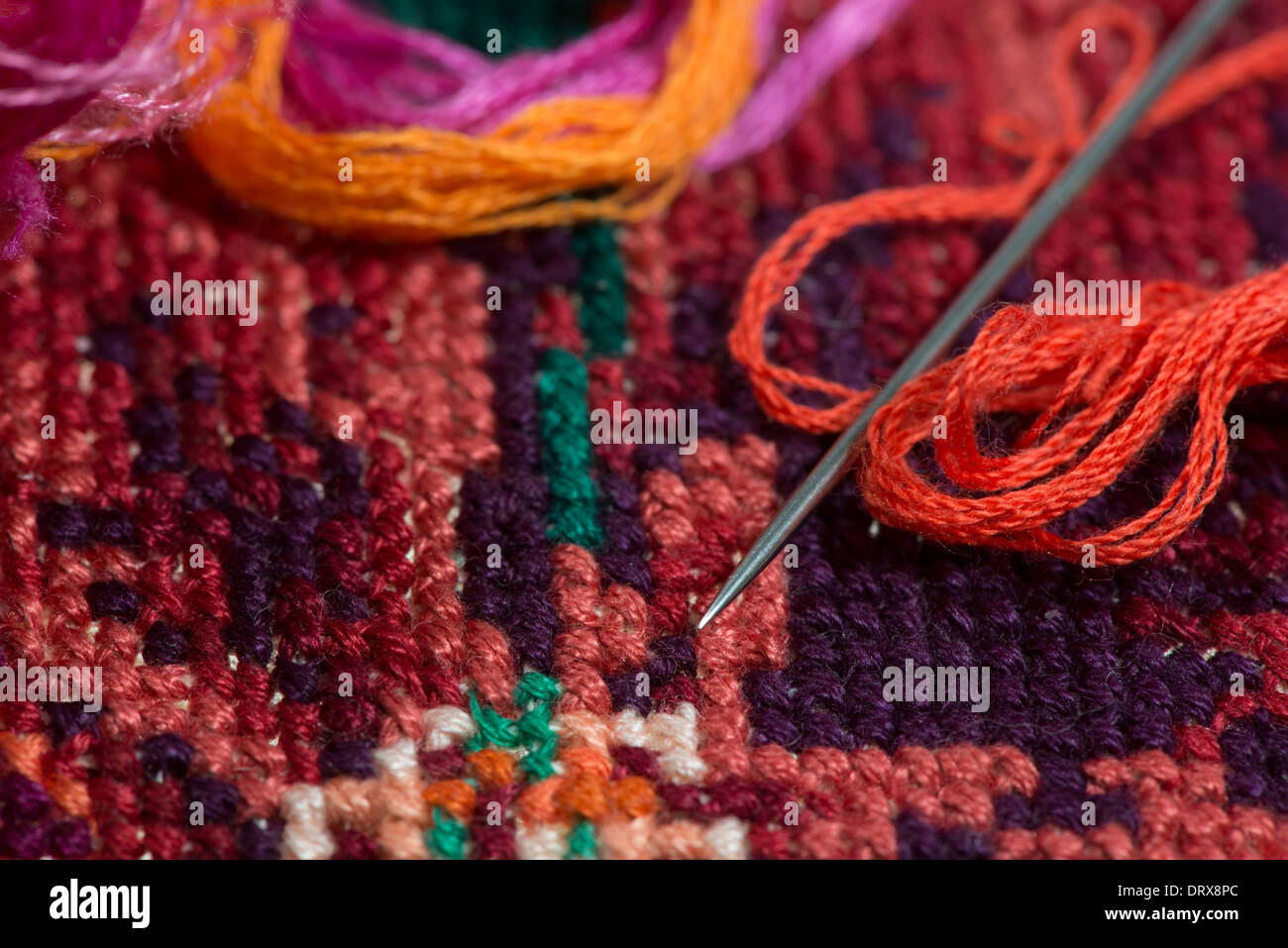 skeins of multicolored threads for embroidery - muline. against the background of cross-stitch - Stock Image