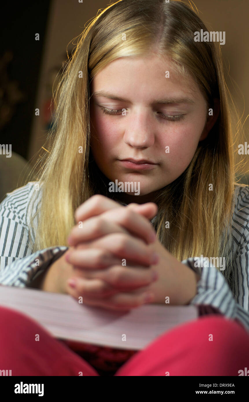 Praying girl bowing her head with hands folded over her bible and her eyes closed. - Stock Image