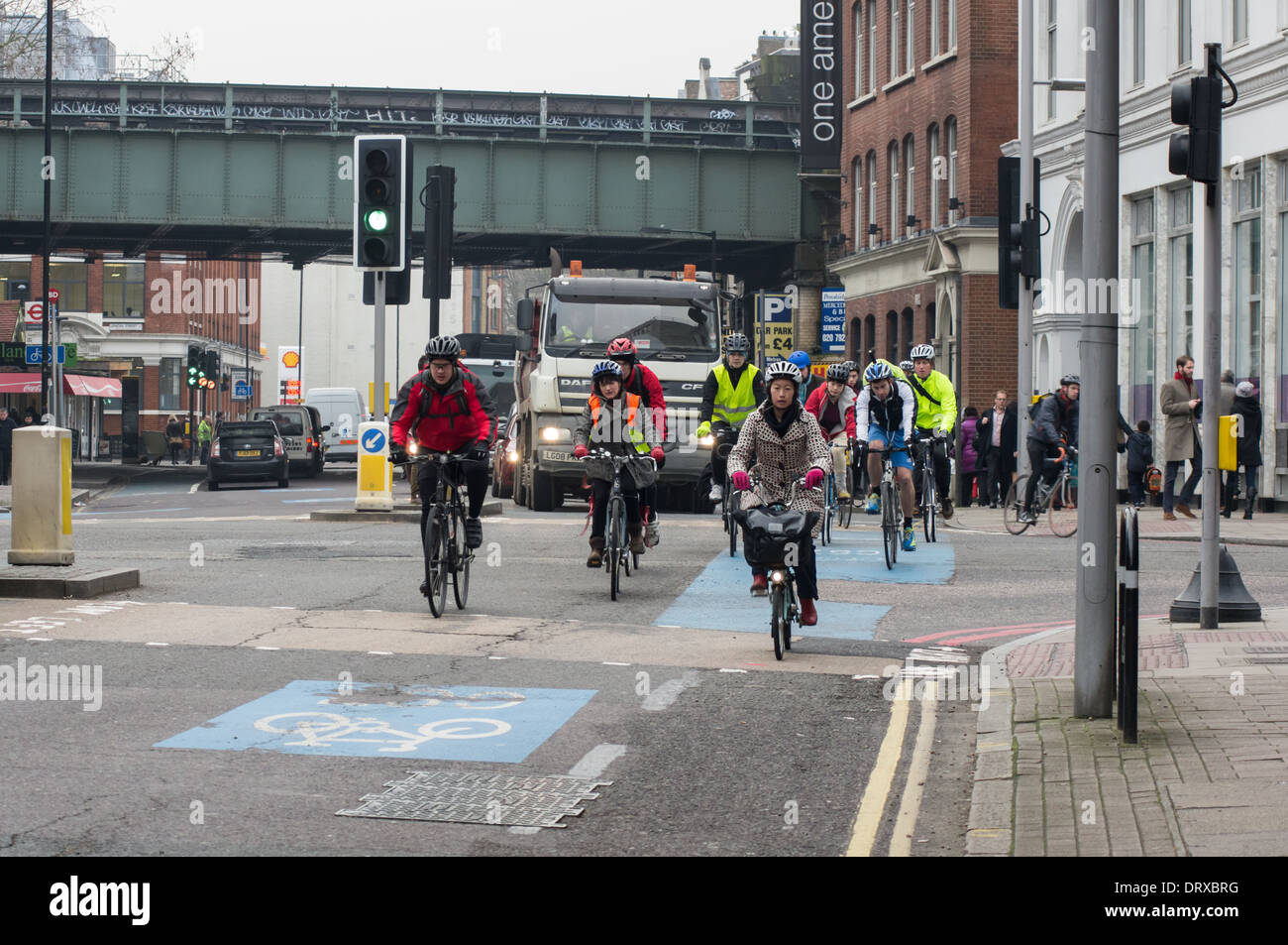People cycling to work in morning rush hour traffic, London England United Kingdom UK - Stock Image