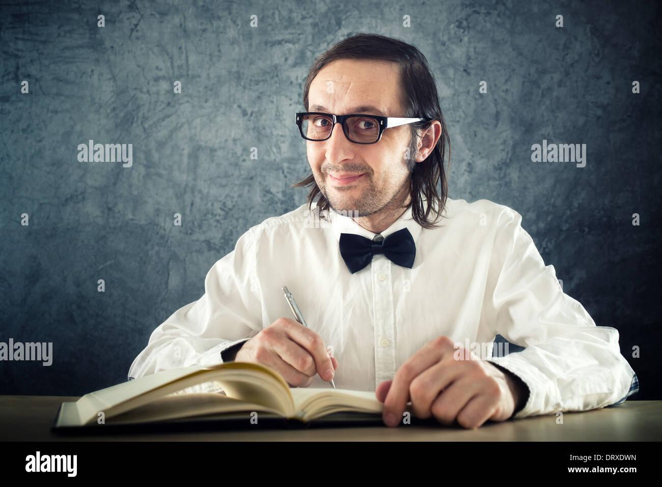Nerd poet writing poems, sitting at work desk. - Stock Image
